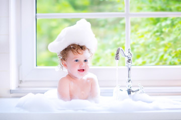 Funny baby girl sitting in big kitchen sink with water and foam