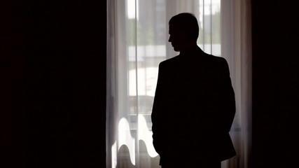 silhouette of stylish man in suit looking out the window