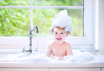 Toddler girl relaxing in big kitchen sink with water and foam