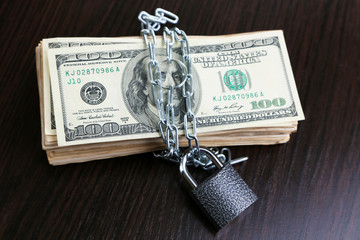 Dollars currency with lock and chain on wooden table