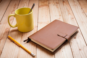 Coffee cup with notebook and pencil