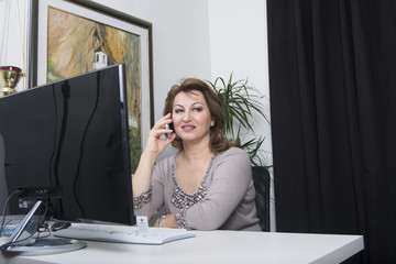 Woman speaking on her mobile phone (desk, office, business)