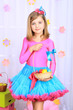 Beautiful small girl in petty skirt holding basket with