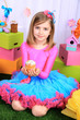 Beautiful small girl in petty skirt holding Easter cake