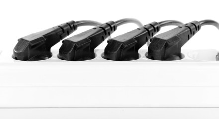 Many plugs plugged into electric power bar close-up