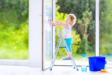 Little girl washing a window with view garden
