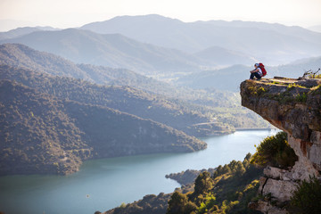 Female hiker sitting on cliff and enjoying valley view