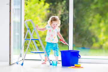 Pretty toddler girl washing a window with view garden