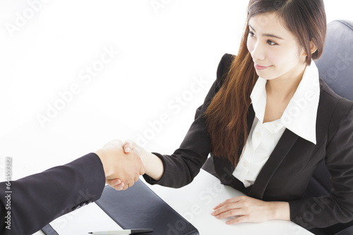 smiling business woman shaking hands with client in her office