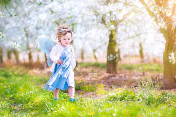 Cute toddler girl running apple in a blooming garden