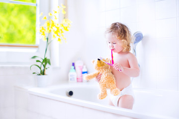 Cute toddler girl brushing teeth with a toy