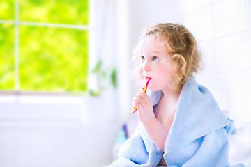 Sweet toddler girl brushing teeth