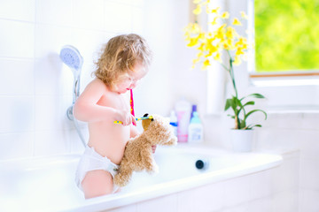 Baby girl brushing teeth playing with a teddy bear