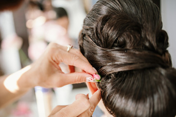 Bridal stylist attaching flower to bride coiffure
