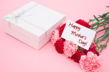 card of happy mother's day and present box and carnations