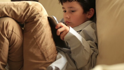 little boy relaxation with digital tablet at home