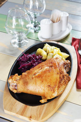 Pork knuckle in a pan with boiled potatoes and beets
