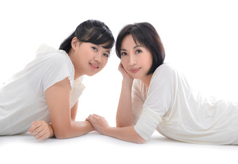 Mother and teenager daughter lying down over white