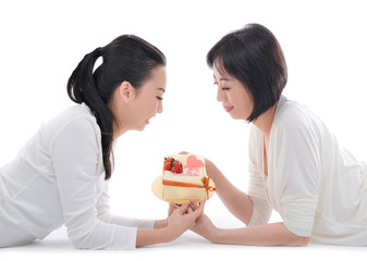 Mother and teenager daughter lying down holding cake