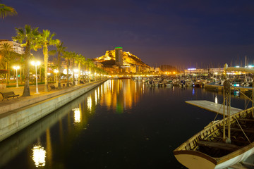 Port with yachts and embankment in night. Alicante