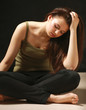 Depressed woman sitting on floor with eyes closed.