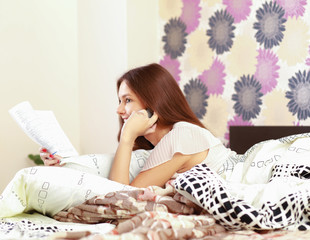 girl lying on a bed with book and a mobile phone