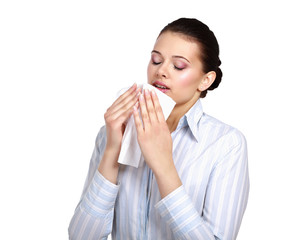 Sick woman blowing her nose, white background.