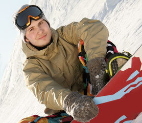 Snowboarder sitting on a ski slope.
