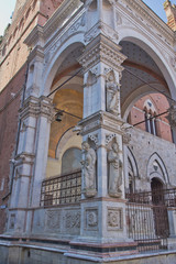 Statues on loggia of the Torre del Mangia. (Siena, Italy)
