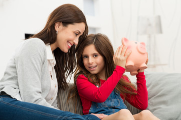 Mother Looking At Daughter Holding Piggybank