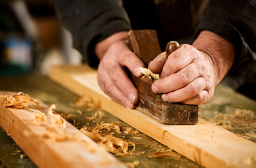Skilled carpenter using a handheld plane