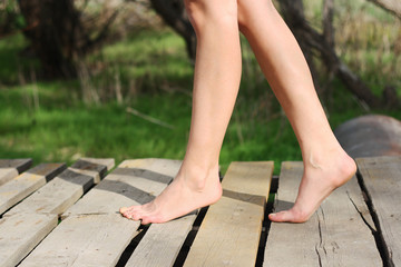 beautiful girl's legs  on the pier spring