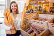 Young and smiling woman with baguettes in the bakery store