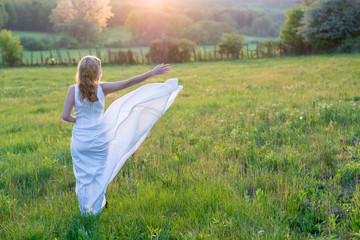 Beautiful young woman enjoying freedom on field at sunset