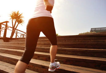 woman runner athlete running on wooden stairs