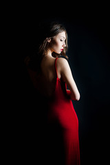 Beautiful young woman in red dress with evening make-up