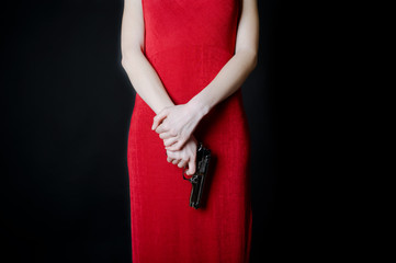 Silhouette of beautiful young woman in red dress holding gun