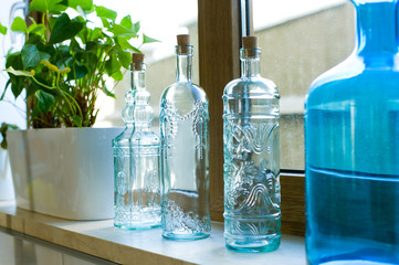 Decorative bottles from blue glass on a windowsill