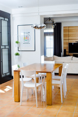 Wooden dining table with white chairs