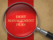 Debt Management Plan. Magnifying Glass on Old Paper.