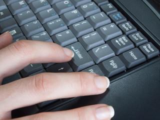 Woman fingers on computer keyboard