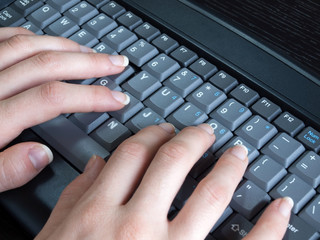 Woman typing on computer keyboard