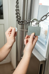 photo of female opening lock with chain on refrigerator