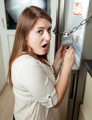 brunette woman trying to open lock on fridge