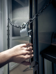 photo of men hand opening fridge locked by chain