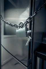 photo of refrigerator locked by chain and metal lock