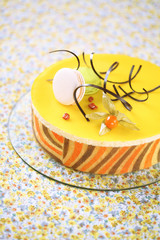 Tropical Mousse Cake (Charlotte) on a yellow floral tablecloth.