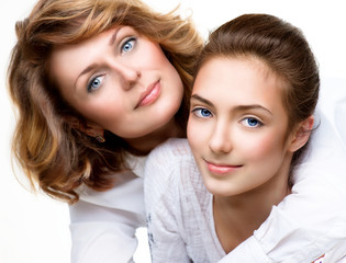 Attractive happy mother and smiling teenage daughter