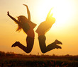 Silhouette of a beautiful girls jumping over sunset