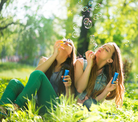 Joyful teenage girls laughing and blowing soap bubbles